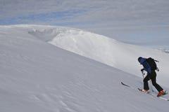 Lo sciatore arrampica la collina. Fotografia Stock