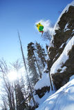 Lo sciatore che salta contro il cielo blu Immagine Stock