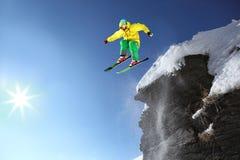 Lo sciatore che salta contro il cielo blu Fotografie Stock
