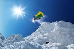 Lo sciatore che salta contro il cielo blu dalla roccia Immagini Stock Libere da Diritti