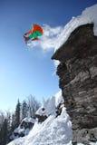 Lo sciatore che salta contro il cielo blu dalla roccia Fotografia Stock