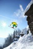 Lo sciatore che salta contro il cielo blu dalla roccia Immagine Stock