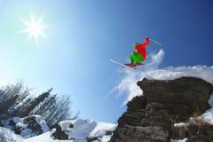 Lo sciatore che salta contro il cielo blu dalla roccia Fotografie Stock Libere da Diritti