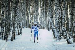 Lo sciatore dell'atleta della ragazza guida sulla pista nello stile del classico della foresta della betulla fotografia stock libera da diritti