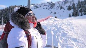 Lo sciatore della donna scala una seggiovia su una montagna in una stazione sciistica archivi video