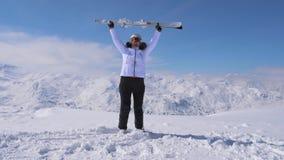 Lo sciatore della donna sta sulla montagna del pendio, alzata lo sci e li ondeggia 4k stock footage