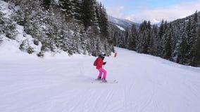 Lo sciatore della donna va giù sui pendii di Ski Route Down Against Mountain fra l'abetaia video d archivio