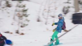 Lo sciatore e lo snowborder si rilassano alla stazione sciistica delle montagne stock footage