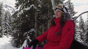 Lo sciatore felice della donna aumenta su sulla località di soggiorno di Ski Lift In The Mountains nell'inverno video d archivio
