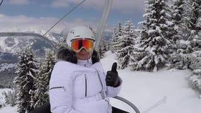 Lo sciatore felice scala la seggiovia alla cima della montagna e mostra il suo pollice su stock footage