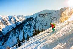 Lo sciatore Freerider discende dalla montagna alla luce della m. Immagine Stock