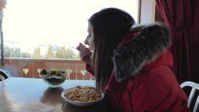 Lo sciatore mangia gli spaghetti ad un caffè nelle montagne nell'inverno video d archivio