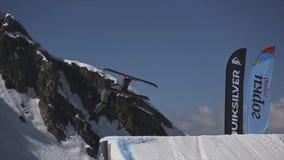 Lo sciatore salta dal trampolino Faccia il salto mortale pericoloso Montagne Giorno pieno di sole stock footage