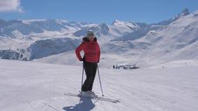 Lo sciatore sportivo della donna sta sul pendio della stazione sciistica della montagna video d archivio
