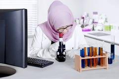 Lo scienziato analizza il prodotto chimico con il microscopio Immagini Stock Libere da Diritti