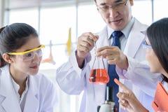 Lo scienziato asiatico dello studente del yound che ricerca e che impara con lo scienziato senior ha fondo d'istruzione in un lab immagini stock