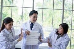 Lo scienziato asiatico senior ha assegnazione del lavoro nuovo agli studenti in laboratorio immagine stock libera da diritti