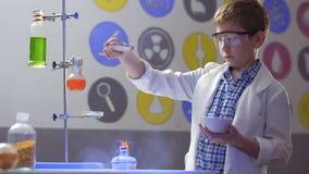 Lo scienziato del ragazzo fa gli esperimenti con amido e fuoco in laboratorio stock footage
