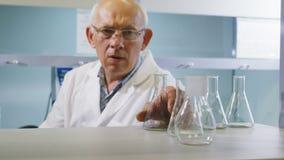 Lo scienziato di mezza età in vetri prende la lampadina dallo scaffale stock footage
