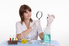 Lo scienziato esamina la medicina tramite una lente d'ingrandimento Fotografie Stock