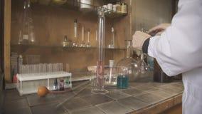 Lo scienziato femminile in un accappatoio mette gli esperimenti facendo uso degli utensili chimici video d archivio