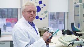 Lo scienziato maschio nota le informazioni sulla lavagna per appunti al laboratorio fotografie stock libere da diritti
