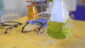 Lo scienziato mescola il liquido di cottura a vapore verde in una boccetta archivi video