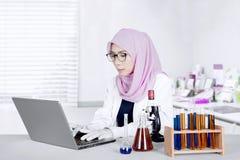 Lo scienziato musulmano lavora con il computer portatile Fotografia Stock