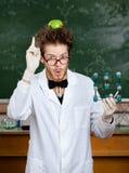 Lo scienziato pazzo con una mela sulla sua testa mostra l'indice mentre passa i modelli molecolari Immagini Stock Libere da Diritti