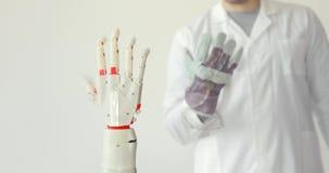 Lo scienziato sta collaudando la mano robot della protesi che ripete il movimento della sua mano in guanto con i sensori muscolo stock footage