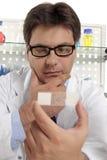 Lo scienziato studia una trasparenza del microscopio Immagine Stock