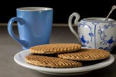 Lo sciroppo olandese delizioso waffles su un piatto bianco con la tazza dello zucchero e del caffè fotografia stock libera da diritti