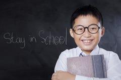 Lo scolaro amichevole tiene il libro nella classe Fotografia Stock
