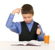 Lo scolaro beve il succo ad uno scrittorio con il diario e la penna Fotografie Stock Libere da Diritti