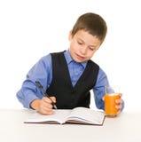 Lo scolaro beve il succo ad uno scrittorio con il diario e la penna Fotografia Stock