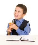 Lo scolaro beve il succo ad uno scrittorio con il diario e la penna Fotografia Stock Libera da Diritti