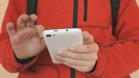 Lo scolaro che tiene un cellulare bianco all'interno video d archivio