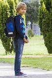 Lo scolaro con i libri e uno zaino pronto vanno a scuola esterno Immagine Stock Libera da Diritti