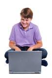 Lo scolaro con il computer portatile ha isolato Fotografie Stock