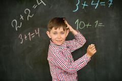 Lo scolaro decide sul bordo il problema con il gesso e ritiene sopra la soluzione, graffia la sua testa immagine stock