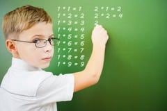 Lo scolaro del primo grado ha scritto la tavola di moltiplicazione sulla lavagna Fotografia Stock