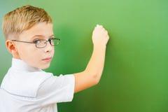 Lo scolaro del primo grado ha scritto sulla lavagna con gesso all'aula Immagine Stock Libera da Diritti