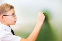 Lo scolaro del primo grado ha scritto sulla lavagna con gesso all'aula Immagini Stock