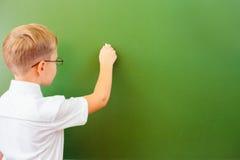 Lo scolaro del primo grado ha scritto sulla lavagna con gesso all'aula Fotografia Stock