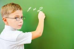 Lo scolaro del primo grado ha scritto sulla lavagna con gesso all'aula Fotografie Stock