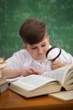 Lo scolaro guarda tramite una lente d'ingrandimento in libro Immagine Stock
