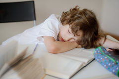 Lo scolaro ha seduta addormentata caduta ad uno scrittorio della scuola Fotografia Stock Libera da Diritti