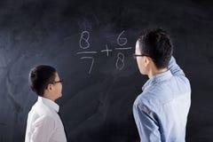 Lo scolaro impara la lezione di per la matematica con l'insegnante Fotografia Stock Libera da Diritti