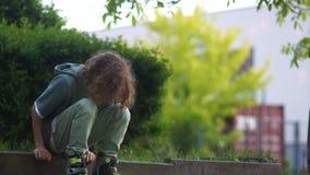 Lo scolaro premuroso triste sui rulli si siede sul bordo, si alza e foglie Rullo teenager, ragazzo riccio video d archivio
