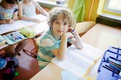 Lo scolaro riccio biondo si siede ad uno scrittorio della scuola nella classe Fotografie Stock